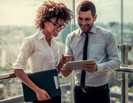Foto de Handsome businessman and beautiful Afro American businesswoman are using digital tablet and smiling while standing on balcony of the office building - Imagen libre de derechos