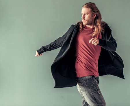 Stylish young man with shoulder-length blond hair and in casual clothes is posing in stylish hooded cardigan, on gray background