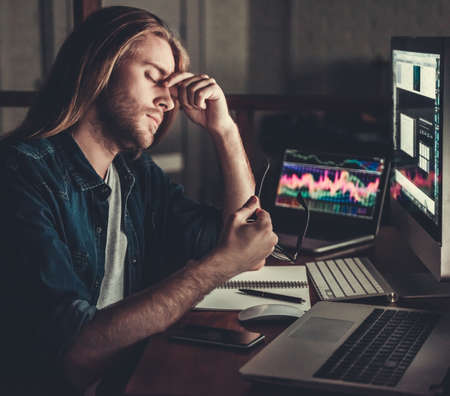 Handsome young businessman with shoulder-length blond hair is massaging nose bridge while working with a computer at night