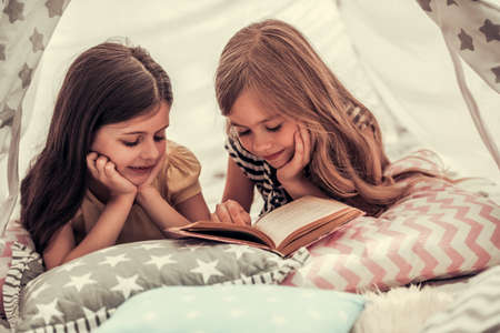Foto de Two cute little girls are reading a book and smiling while playing together in child's teepee - Imagen libre de derechos