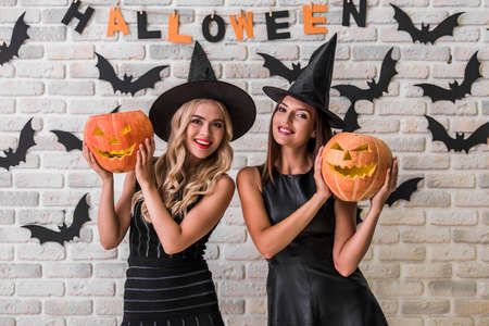 Foto de Beautiful girls in black dresses and witch hats are holding scary pumpkins, looking at camera and smiling on background decorated for Halloween - Imagen libre de derechos