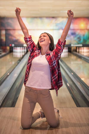 Photo pour Beautiful girl is raising hands in fists and smiling while standing on her knees on bowling alley - image libre de droit