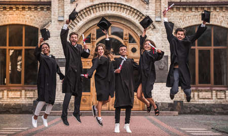 Photo for Successful graduates in academic dresses are holding diplomas, looking at camera and smiling while jumping for the photo outdoors - Royalty Free Image
