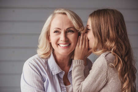 Photo pour Beautiful granny is smiling while teenage granddaughter is whispering her something - image libre de droit