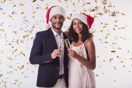 Elegant Afro American couple in Santa hats clinking glasses of champagne, looking at camera and smiling, on white background
