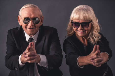 Beautiful old couple in elegant clothes and glasses is holding hands together imitating guns, looking at camera and smiling, on gray background