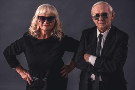 Beautiful old couple in elegant clothes and glasses is holding hands looking seriously at camera, on gray background