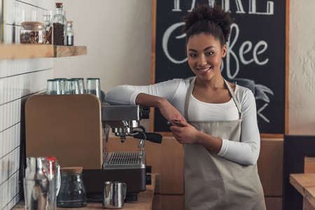 Photo pour Beautiful Afro American barista in apron is looking at camera and smiling while leaning on the coffee machine - image libre de droit
