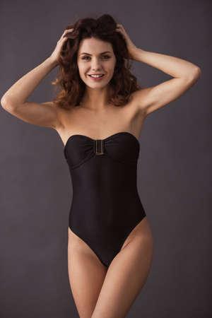 Foto de Portrait of a young beautiful sexy girl in a swimsuit on a black background - Imagen libre de derechos