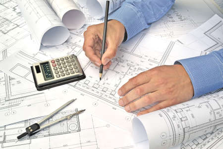 Foto de Hands of engineer working with the tool on project drawings background - Imagen libre de derechos