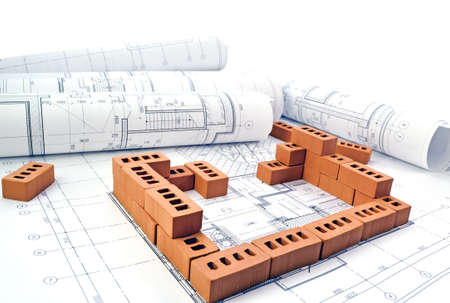 Photo pour Bricks for building a house with design drawings - image libre de droit