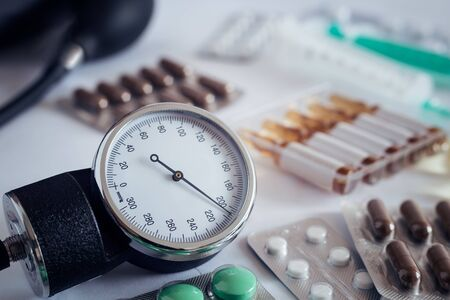 On the table is an apparatus for blood pressure measurement, which shows higher pressures. It's a hypertensive crisis. Near are medications to assist.
