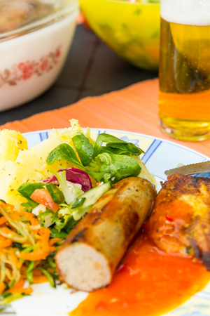 Sausage, salads and potato lying on the plate to eat.