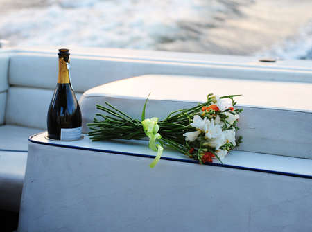 champagne and bouquet on the white boat