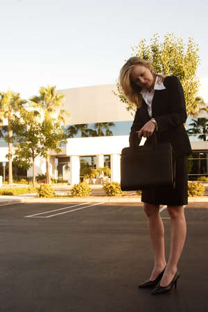 Business woman looking through briefcase outside an office building