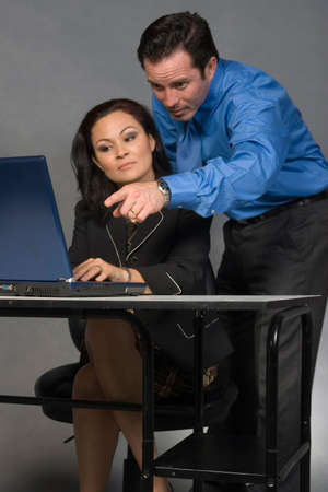 Business man standing behind a woman coworker sitting at her desk pointing at the computer screen