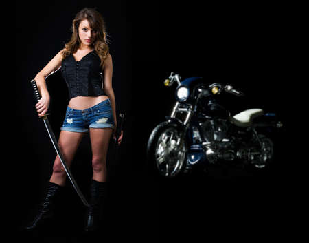 Attractive sexy woman in shorts holding a samurai sword standing beside a harley motorcycle on black