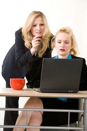 Two women office workers one sitting at desk one standing behind her both looking at a computer screen with serious expressions