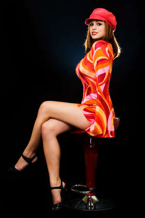 Full body of a beautiful woman with blond hair wearing bright colored seventies style dress and red hat sitting on stool on black background