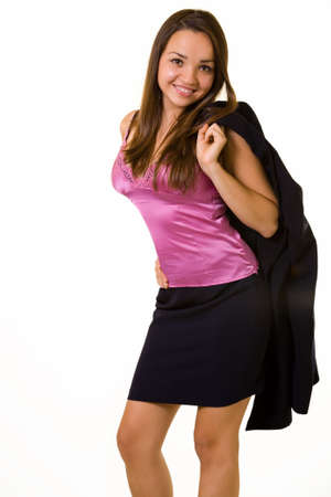 Attractive young brunette woman wearing business suit with jacket slung over shoulder wearing a hot pink satin undershirt standing with a happy expression on white