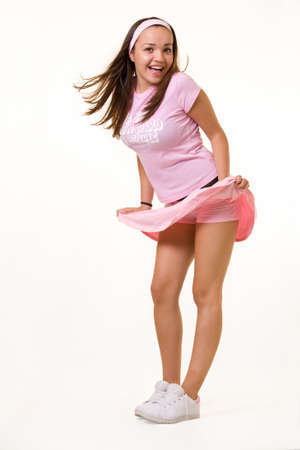 Full body of an attractive young woman with brunette hair in a short pink tennis outfit with wind blowing up skirt with happy excited expression