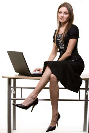 Full body of a young brunette business woman sitting on office desk beside laptop computer over light background