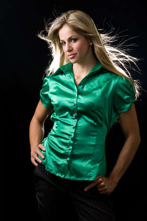 Beautiful young woman with blond hair wearing shiny green satin blouse posing on black background