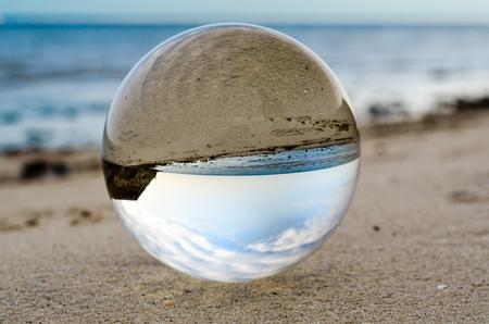 Foto de glass crystal ball lens lies on the sand of the sea shore - Imagen libre de derechos