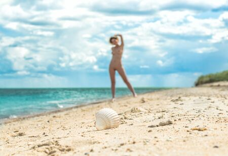 Photo for young nude girl with a hat walks on an empty beach near the sea surf against the blue sky with clouds in summer - Royalty Free Image