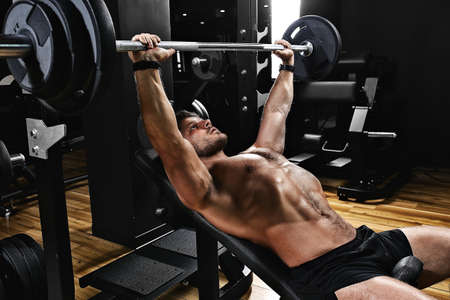Photo for handsome young man doing bench press workout in gym, Fitness motivation, sports lifestyle, health, athletic body, body positive. Film grain, selective focus - Royalty Free Image