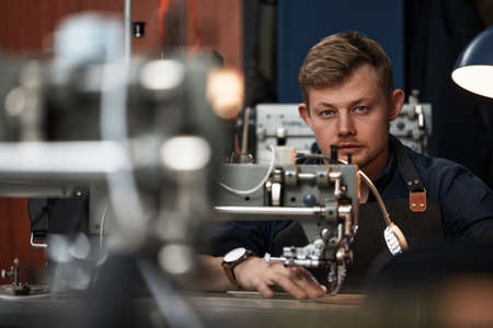 Photo pour Working process of leather craftsman. Tanner or skinner sews leather on a special sewing machine, close up.worker sewing on the sewing machine - image libre de droit