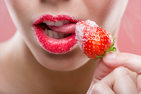 Beautiful female red lips, full with Granulated sugar, lick strawberry