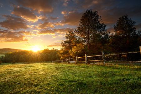 Photo pour Picturesque landscape, fenced ranch at sunrise - image libre de droit