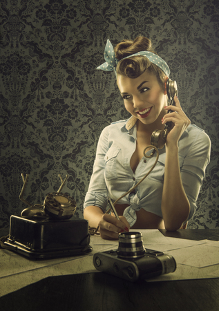 Vintage style  Woman talking on the phone with retro dial phoneの写真素材
