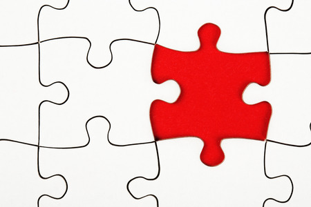 Missing piece in a puzzle on red background, business conception