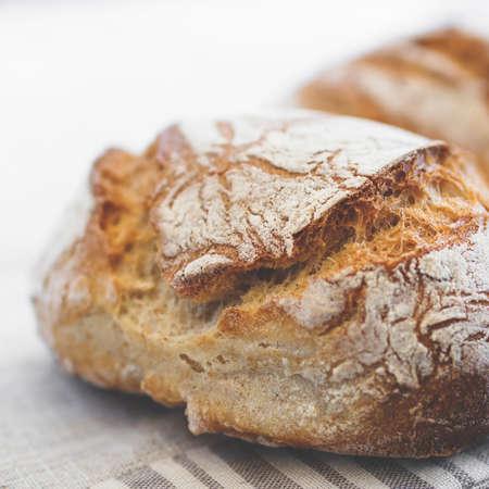 Foto für Tasty loaf of bread on table cloth. Extreme close-up of rustic Italian bread. Shallow DOF. - Lizenzfreies Bild