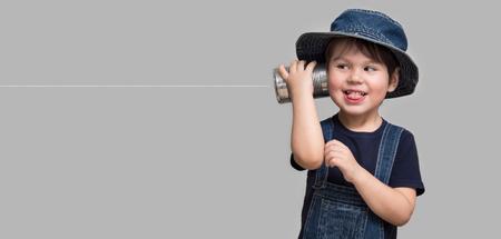 Foto de A small boy attached a telephone from a tin can to his ear - Imagen libre de derechos