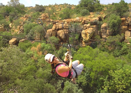 Lady sliding on a zip line across a gorge in South Africa