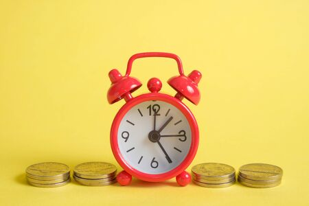 Photo pour The concept of saving money in a crisis. A red vintage clock stands on a stack of coins on a yellow background. - image libre de droit