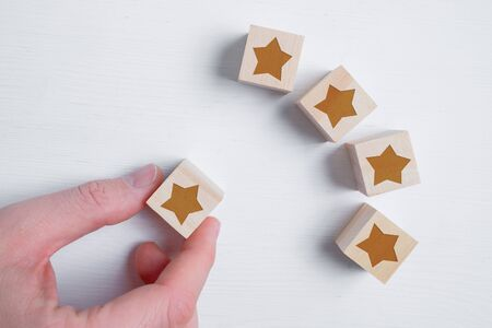 Photo for A man decides with his hand to put five stars or not on wooden cubes showing the best rating. Best score. Flat lay. Close up. - Royalty Free Image
