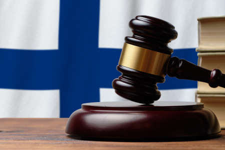 Photo pour Justice and court concept in Republic of Finland. Judge hammer on a flag background. - image libre de droit