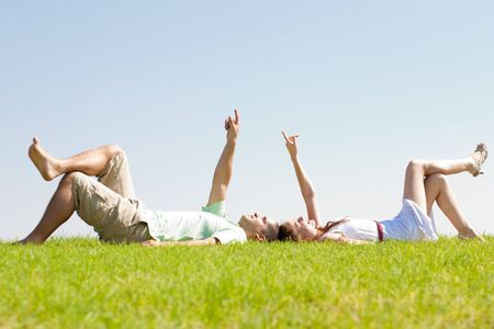 young couple lie down on grass and point to the sky, outdoor at park