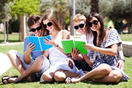 Young couples relaxing in the park and reading books and smiling at camera