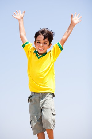 Young kid with raised arms posing in front of camera