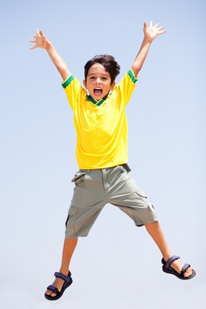 Smart kid jumping high in air, arms stretched and looking at camera