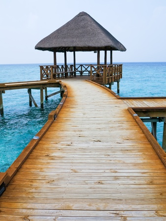 Breath taking view of a wooden walkway leading to the isolated gazebo.