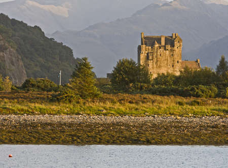ancient castle in scotland with forest and mountains in background