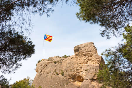 Spanish flag (Estelada) on the mountain in the forest. Against the background of the blue sky, Catalunya, Spain. Copy space