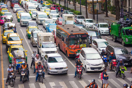 BANGKOK, TAILAND - NOVEMBER 28, 2016 : Vehicles (motorcycle, bus, car and taxi) wait for a green light at intersection with crosswalk on the city road