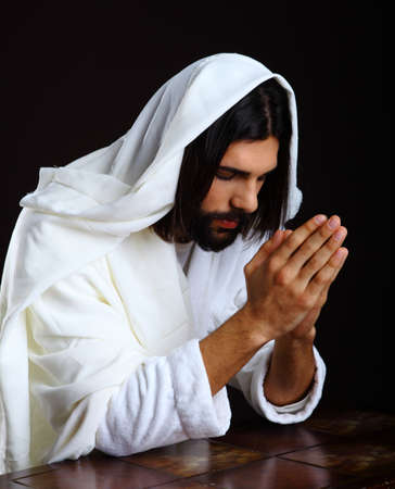 Praying Jesus Christ of Nazareth kneeling hands together